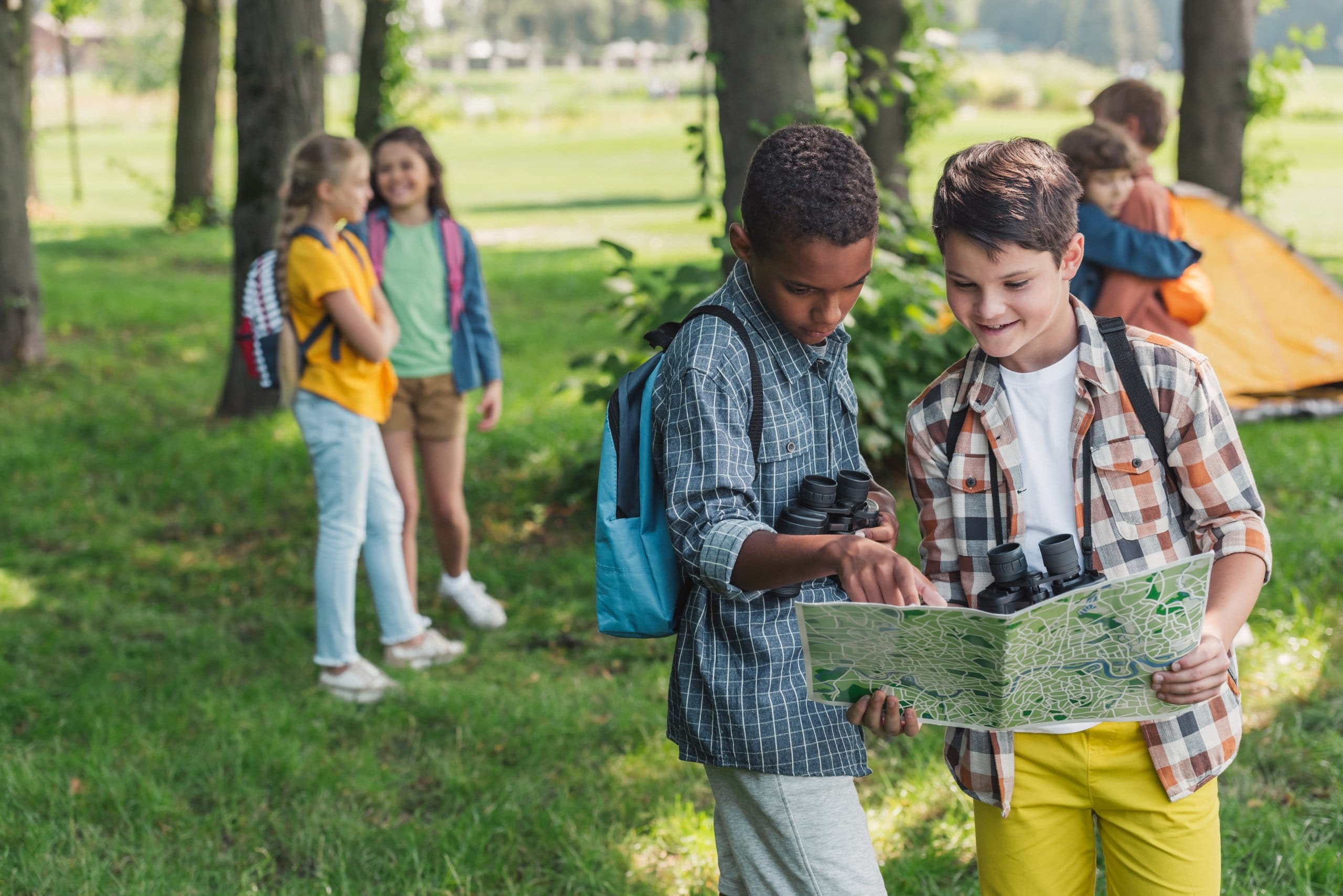 selective focus of african american kid looking at map near friend